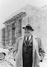 A photo of Herman B Wells standing in front of an unfinished Lilly Library